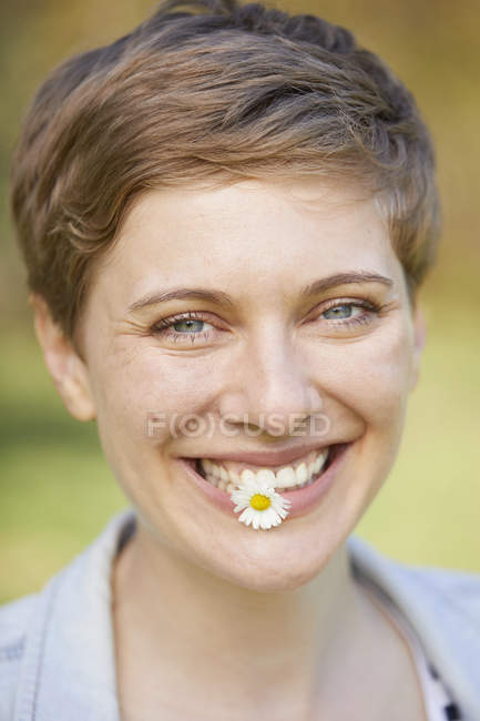 Portrait of laughing woman with daisy in mouth — Stock Photo