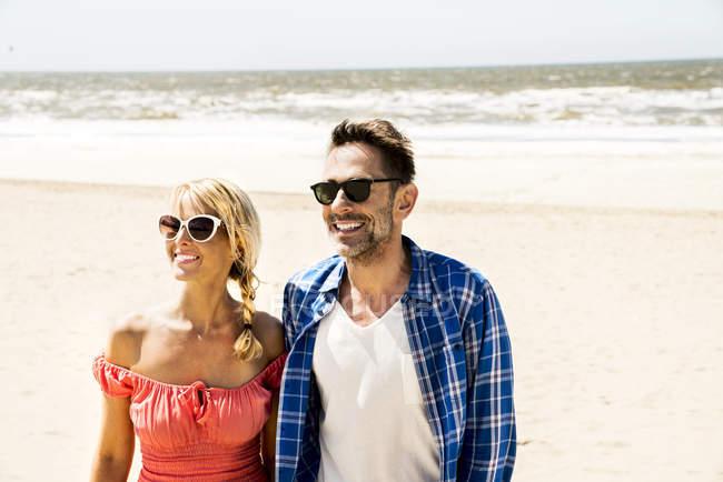 Casal feliz usando óculos de sol na praia — Fotografia de Stock