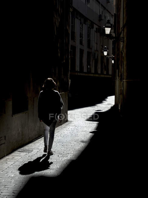Spain, Palma de Mallorca, woman walking in alley — Stock Photo