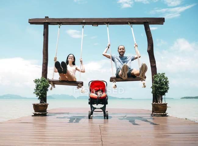 Tailandia, Koh Lanta, padres felices en columpios de madera frente al mar y bebé durmiendo en un cochecito - foto de stock