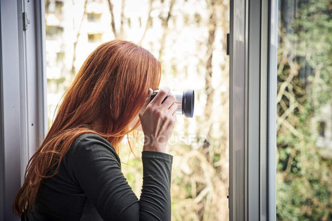 Redheaded woman leaning out of window taking photo with camera — Stock Photo