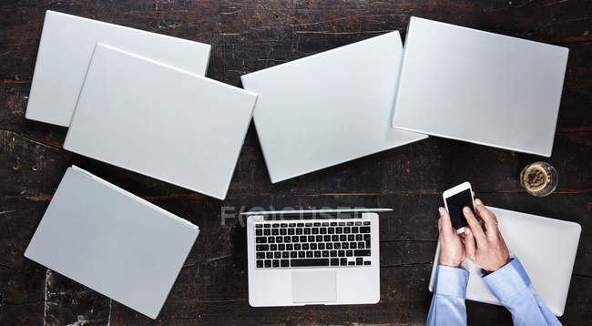 Man's hands using smartphone on table with seven laptops, top view — Stock Photo
