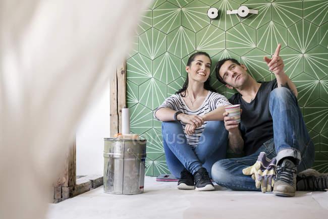 Couple renovating new house, sitting on ground planning bathroom — Stock Photo