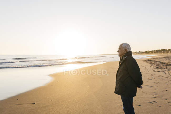 Senior man looking at sea and standing on sandy beach — Stock Photo