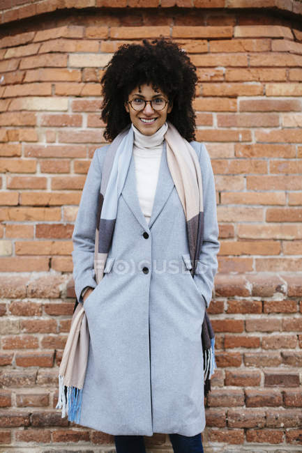 Portrait of smiling woman in coat standing against brick wall — Stock Photo