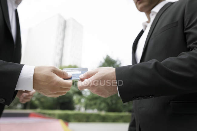 Two businessmen handing over credit card — Stock Photo