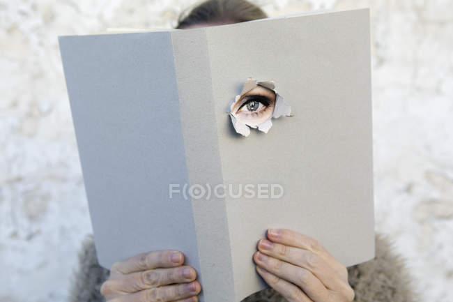 Жінка покриває обличчя книжкою, читає вірші, дивиться крізь обкладинку — стокове фото