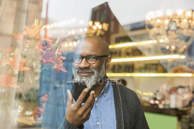Porträt eines lächelnden afrikanisch-amerikanischen Mannes mit Handy hinter Fensterscheibe — Stockfoto