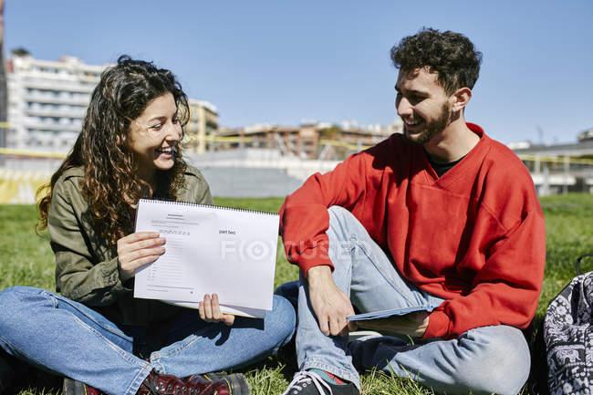 Два счастливых студента сидят в парке и учатся вместе. — стоковое фото