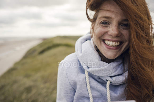 Rothaarige Frau genießt frische Luft am Strand — Stockfoto