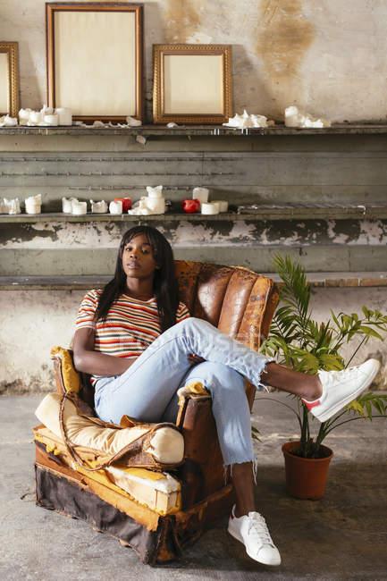 Ritratto di giovane donna fresca seduta su una vecchia sedia in pelle in un soppalco — Foto stock