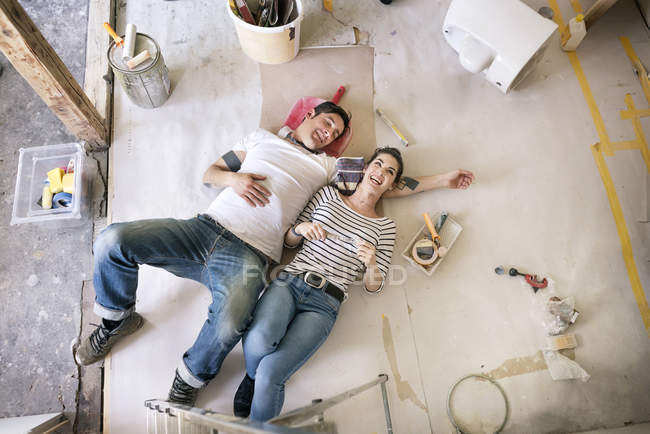 Happy couple renovating new home, taking a break, daydreaming — Stock Photo