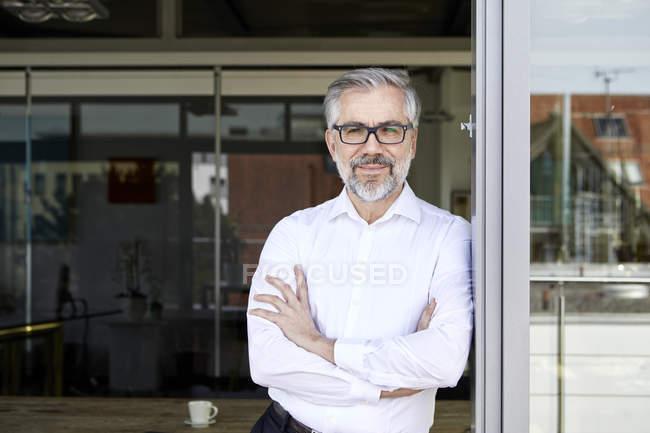 Retrato de um empresário sorridente em pé à porta francesa — Fotografia de Stock