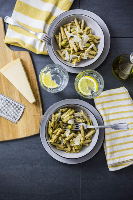 Whole-grain noodles with green pesto and olives — Stock Photo