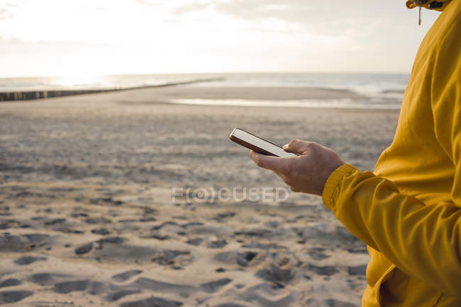 Man in yellow jacket, using smartphone on the beach — Stock Photo