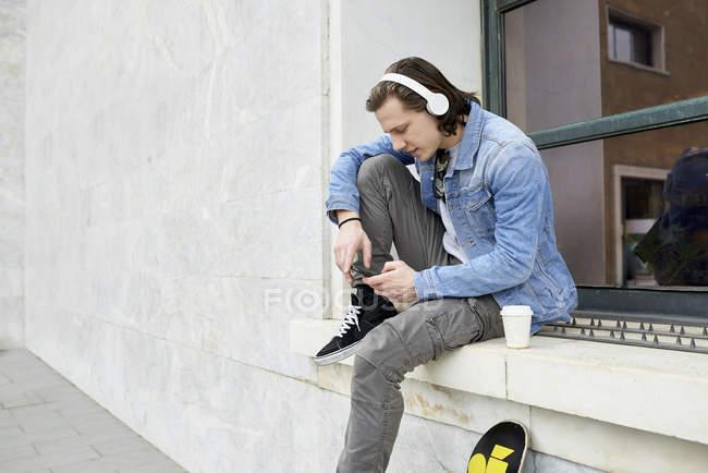 Молодой человек сидит на подоконнике, ждет, используя смартфон — стоковое фото