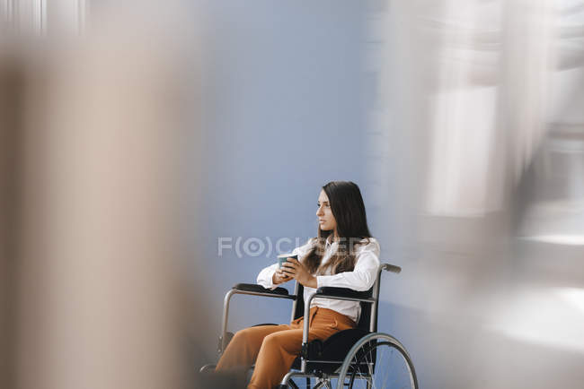Young handicapped woman sitting in wheelchair, looking worried — Stock Photo