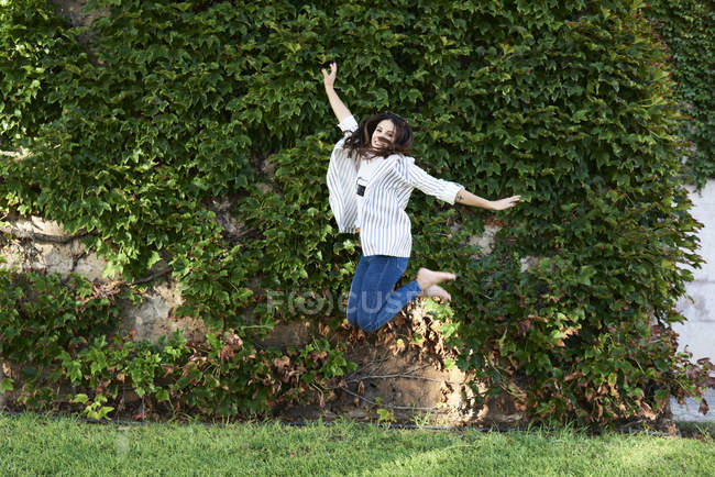 Happy young woman jumping in the air outdoors — Foto stock