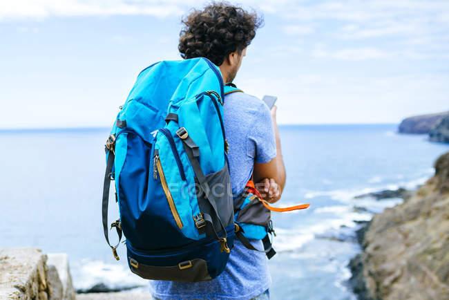 Spagna, Isole Canarie, Gran Canaria, Primo piano dell'uomo con lo zaino con il cellulare — Foto stock