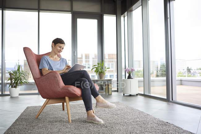 Donna seduta in poltrona a casa con tablet — Foto stock