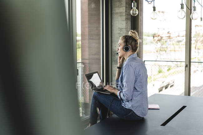 Young businesswoman sitting at desk, making a call, using headset and laptop — Stock Photo
