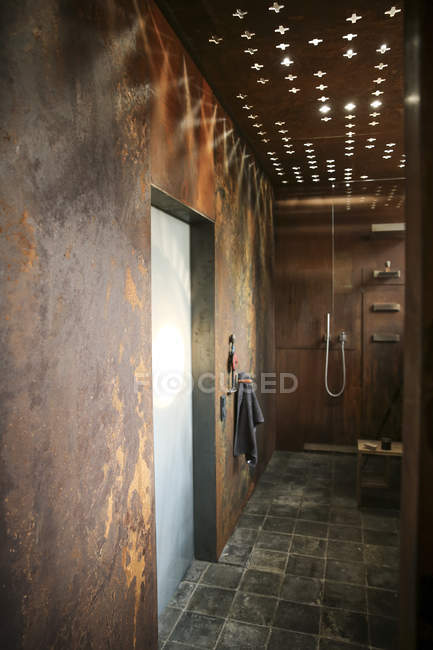 Современная ванная комната с облицовкой стен из кортена и световыми эффектами потолка — стоковое фото