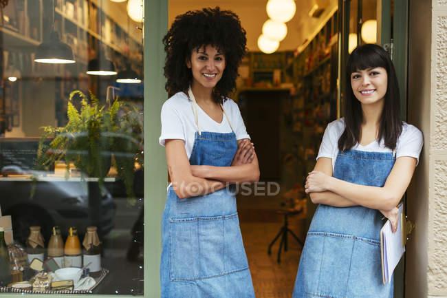 Portrait de deux femmes souriantes debout dans la porte d'entrée d'un magasin — Photo de stock