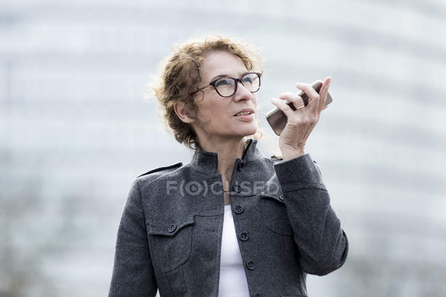 Woman using smartphone outdoors — Stock Photo