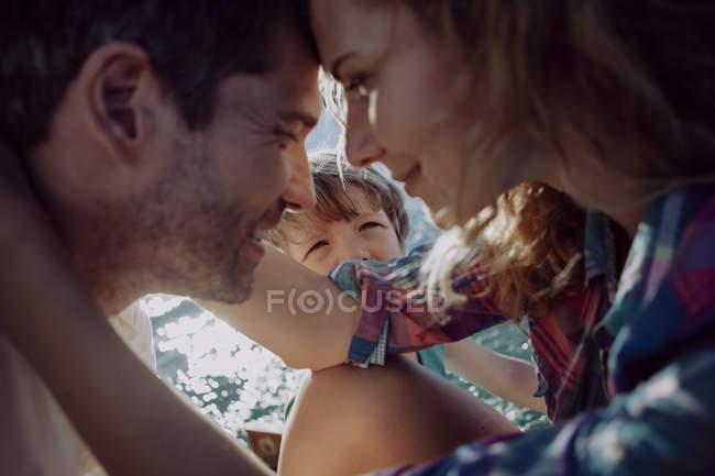 Pareja cariñosa con hijo en un lago - foto de stock