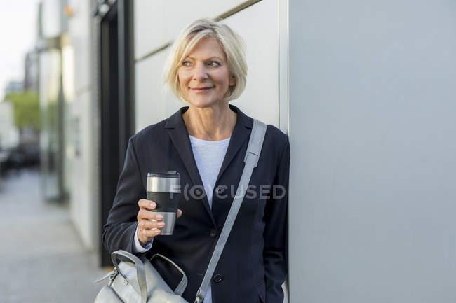 Lächelnde Seniorin mit Kaffee zum Mitnehmen im Freien — Stockfoto