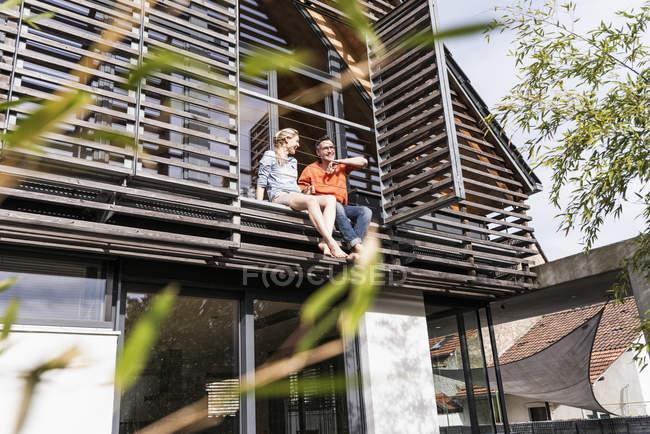 Зрелая пара отдыхает вместе на балконе своего дома — стоковое фото