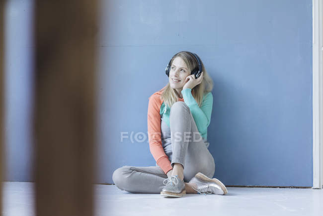 Portrait of smiling woman sitting on floor in front of blue wall and listening music with wireless headphones — Stock Photo