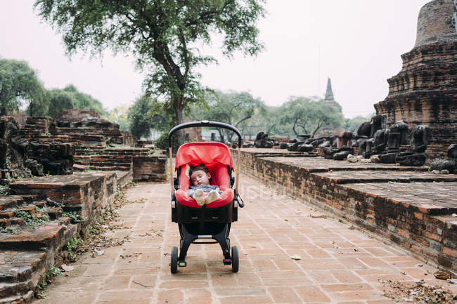 Таїланд, Аюттхая, маленька дівчинка, що спить глибоко на колясці в оточенні руїн і статуй Будди — стокове фото