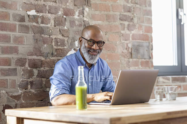 Portrait of laughing african american businessman working on laptop — Stock Photo