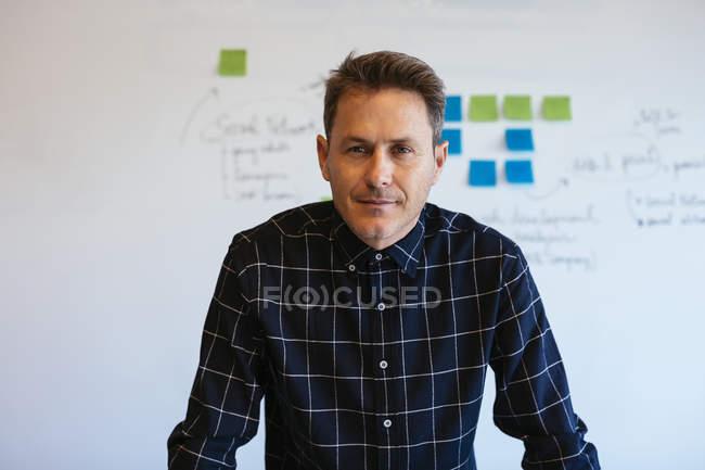 Portrait d'un homme d'affaires confiant au bureau devant un tableau blanc avec des notes adhésives — Photo de stock