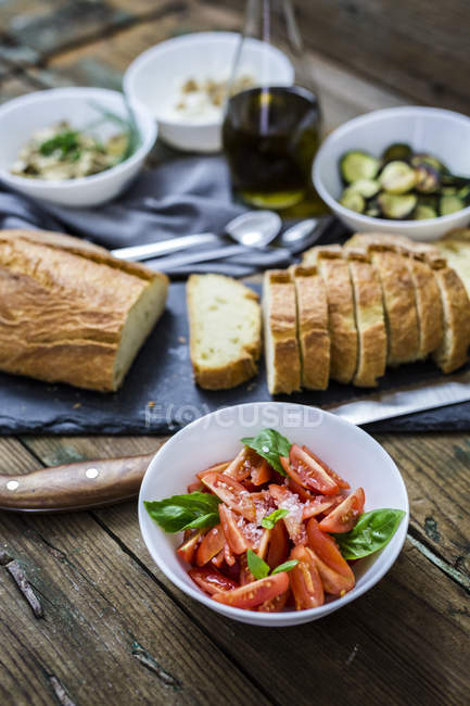 Bruschetta and various ingredients, bread and tomato with basil in a bowl — Stock Photo