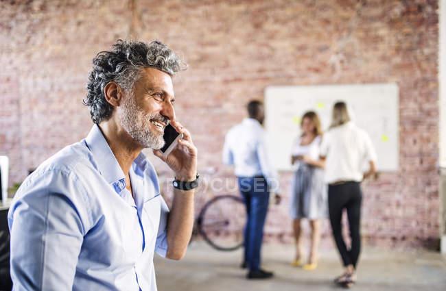 Улыбающийся бизнесмен на мобильный телефон в офисе с коллегами в фоновом режиме — стоковое фото