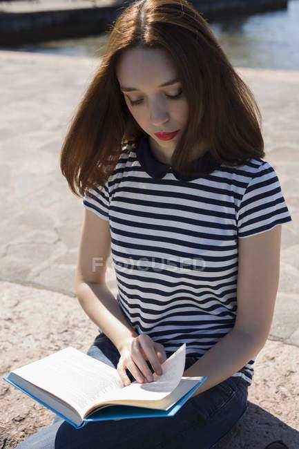 Портрет молодой женщины, сидящей на стене и читающей книгу — стоковое фото