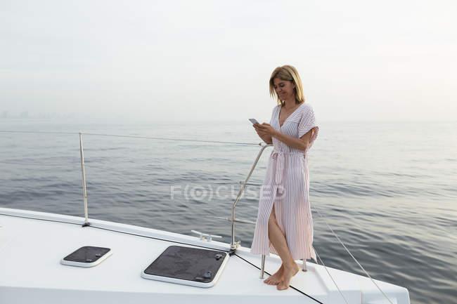 Літня жінка стоїть на катамарані, використовуючи смартфон — стокове фото