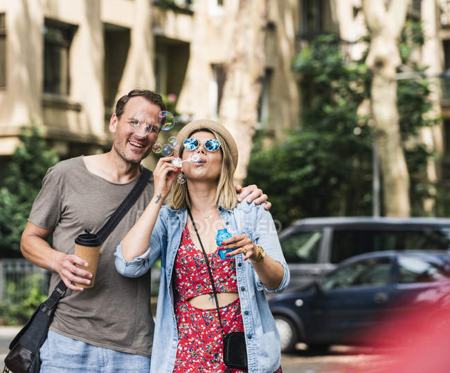Счастливая пара с кофе, чтобы пойти дуть мыльные пузыри в городе — стоковое фото