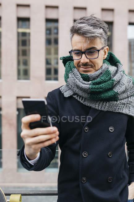 Портрет усміхнений чоловік дивиться на стільниковий телефон в місті — стокове фото