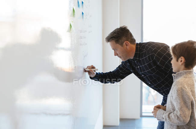 Businessman in office writing on whiteboard with son watching — Stock Photo