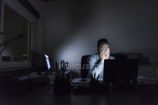 Измученный бизнесмен сидит ночью за рабочим столом — стоковое фото