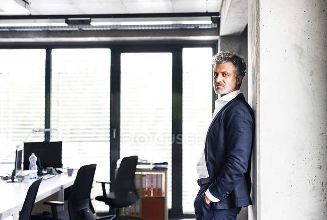 Portrait of confident mature businessman standing in office — Stock Photo