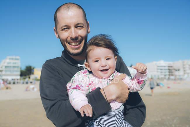 France, La Baule, portrait de père heureux avec bébé fille sur la plage — Photo de stock