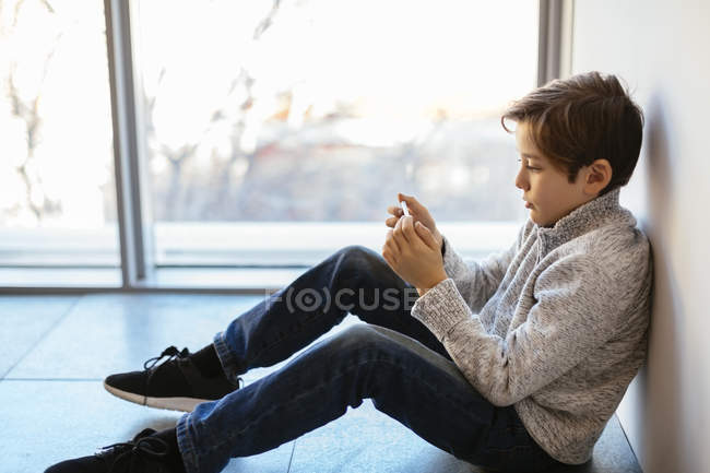 Boy sitting on floor and using cell phone — Stock Photo