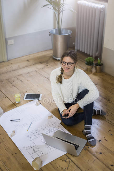 Smiling woman sitting on floor with blueprint, cell phone and laptop — Stock Photo