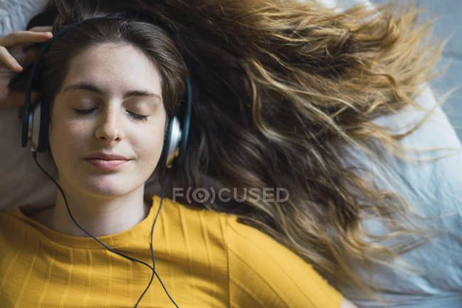Ritratto di giovane donna sorridente sdraiata sul letto ad ascoltare musica con le cuffie — Foto stock