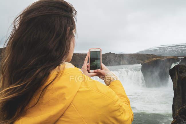 Ісландія, жінка беручи стільниковий телефон зображення водоспаду Годафосс — стокове фото