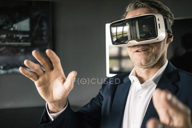 Зрелый бизнесмен в очках VR в офисе — стоковое фото